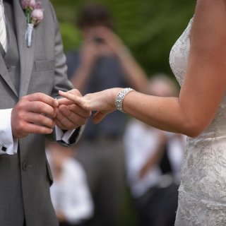 Groom placing a ring on a brides finger in the Gardens