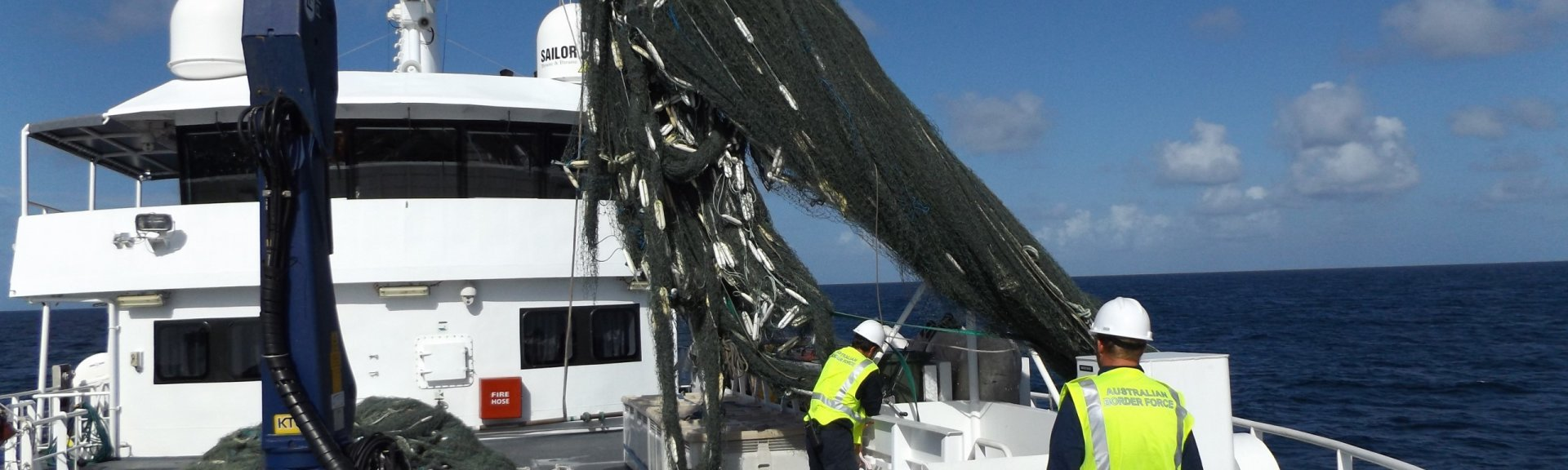 Staff pull ghost net out of the ocean onto a boat. Credit: Australian Fisheries Management Authority
