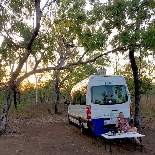 A camper relaxing at sunset at Gungurul Campground