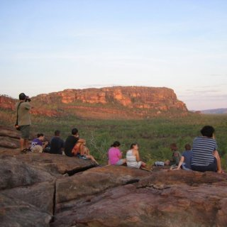 Visitors sitting at Nawurlandja looking out over the escarpment