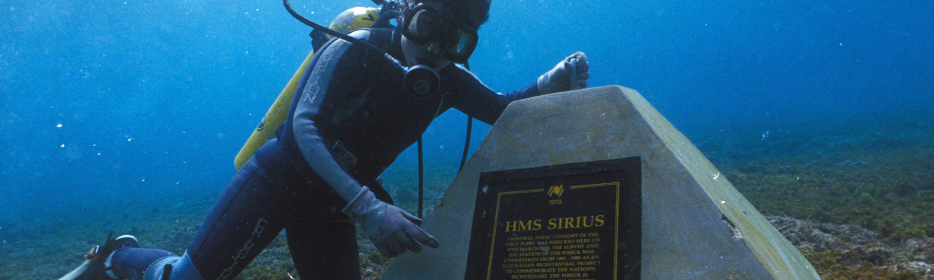A diver alongside a commemorative marker near the HMS Sirius shipwreck site off Norfolk Island.