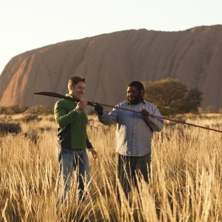 Visitor learning about traditional spears. Photo: Tourism Australia