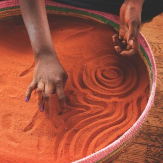 Hands drawing symbols in a large basket of sand. Photo: Tourism NT