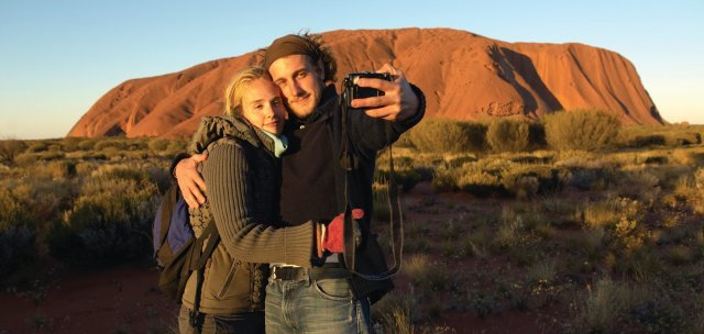 Couple taking a selfie in front of Uluru. Photo: Tourism NT.
