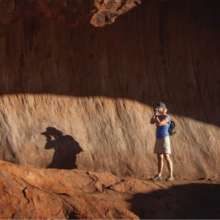 Woman with a digital camera taking a long shot of Uluru