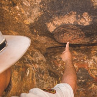 Anangu ranger Mick Starkey pointing out rock art at Mutitjulu Cave. Photo: Grenville Turner
