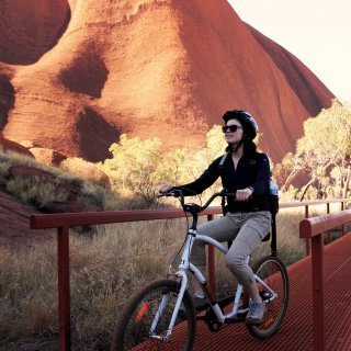Cycling the base of Uluru. Photo: Tourism NT