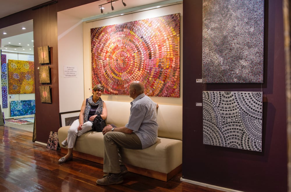 Couple on a seat in front of Aboriginal artworks hanging on gallery wall